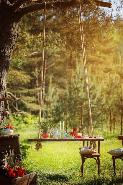 Dekor romantisches abendessen mit kerzen, blumen im grünen wald bei herrlichem sonnenuntergang. Premium Fotos