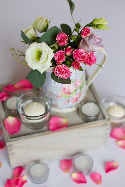 Dekoration von blumen in eisenvase auf dem tisch und flachen weißen kerzen Premium Fotos