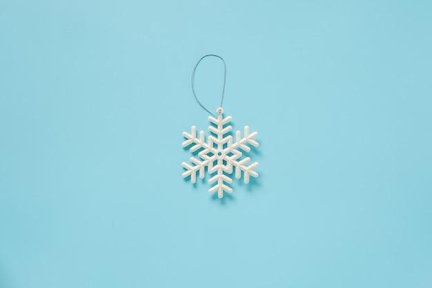 Dekorationsschneeflockenspielzeug der weißen weihnacht auf blauem hintergrund mit kopienraum Premium Fotos