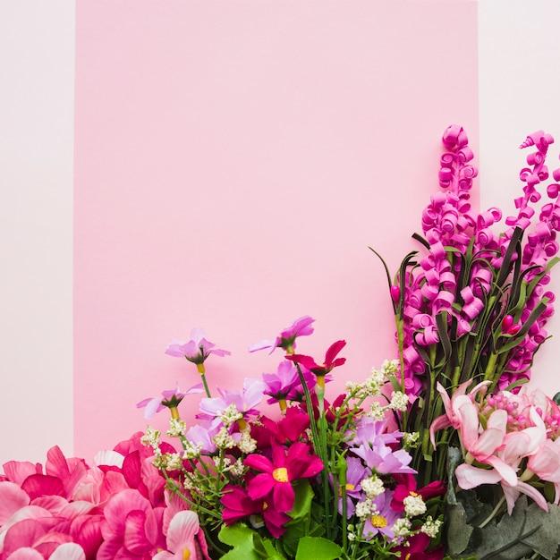 Dekorative bunte gefälschte blumen gegen rosa hintergrund Kostenlose Fotos