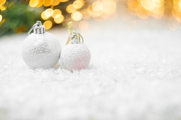 Dekorative weihnachtskugeln, die in einem schnee mit gelbem lichtbokeh liegen Premium Fotos