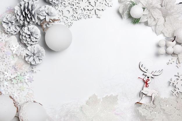 Dekorative weihnachtszusammensetzung von spielzeugen auf einem weißen tischhintergrund. draufsicht. flache lage Kostenlose Fotos