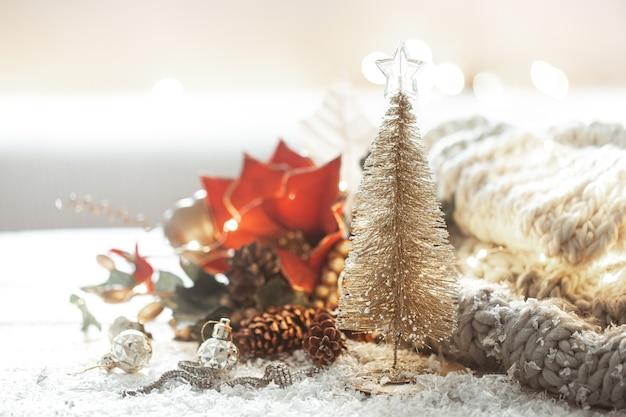 Dekorativer glänzender weihnachtsbaum auf unscharfem hintergrund von dekordetails mit bokeh. Premium Fotos