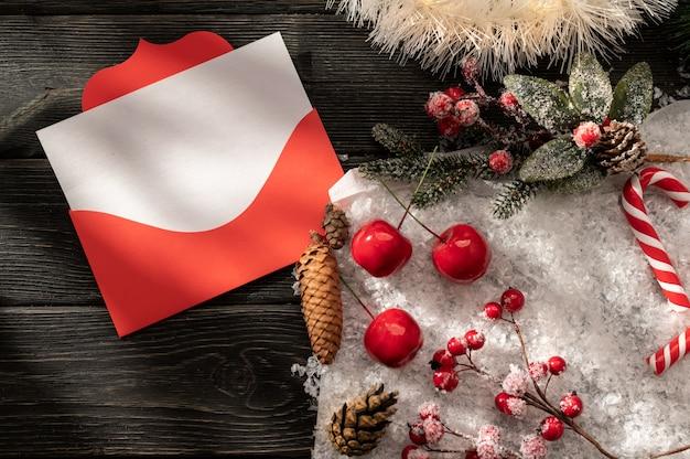 Dekorativer weihnachtshintergrund mit einem roten weihnachtsumschlag und einem leeren weißen blatt Premium Fotos