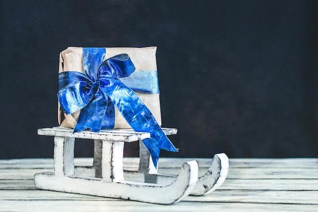 Dekorativer winterschlitten. weißer schlitten. ein geschenk auf einem schlitten. Premium Fotos