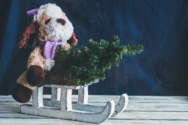 Dekorativer winterschlitten. weißer schlitten. ein stofftier und ein weihnachtsbaum auf einem schlitten Premium Fotos