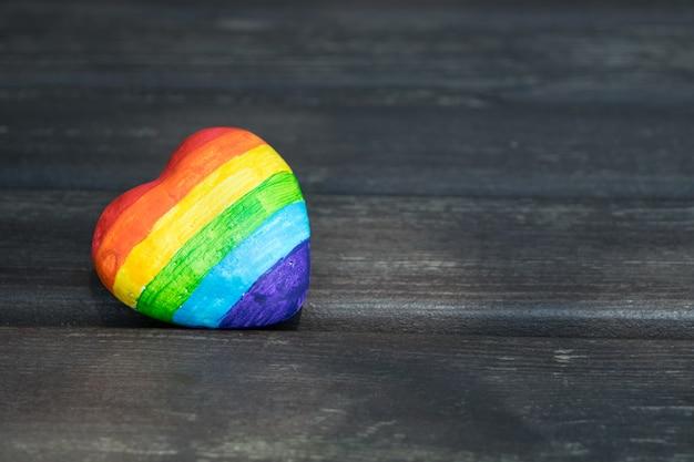 Dekoratives herz mit regenbogenstreifen auf dunklem hölzernem hintergrund. lgbt-stolzflagge. menschenrechte. Premium Fotos