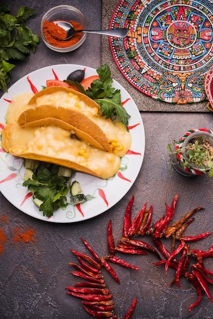 Dekoratives mexikanisches symbol an bord nahe getrocknetem paprika und pita mit dem füllen auf platte Kostenlose Fotos