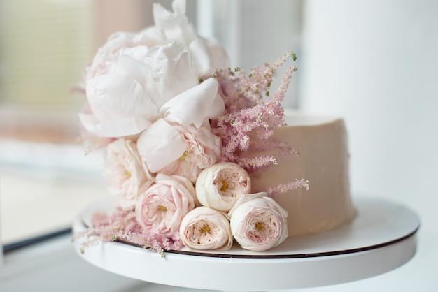 Dekoriert mit frischen blumen, weißem nacktem kuchen, einem stilvollen kuchen Premium Fotos