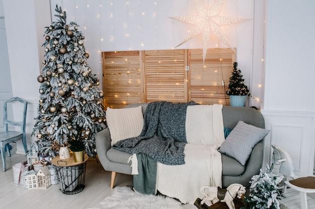 Dekoriertes weihnachtsinterieur. weihnachtsbaum mit geschenkboxen in einem weißen raum. tannenbaum mit girlanden verziert. dekor. fröhliche weihnachten. das konzept der winterferien. Premium Fotos
