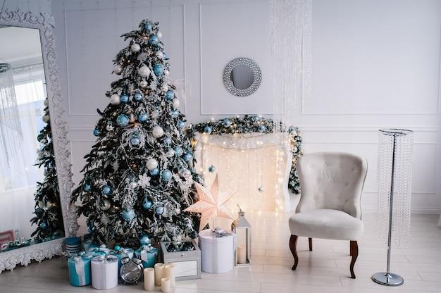 Dekoriertes weihnachtsinterieur. weihnachtsbaum mit geschenkboxen in einem weißen raum. tannenbaum, sessel, kamin mit girlanden verziert. dekor. fröhliche weihnachten. Premium Fotos