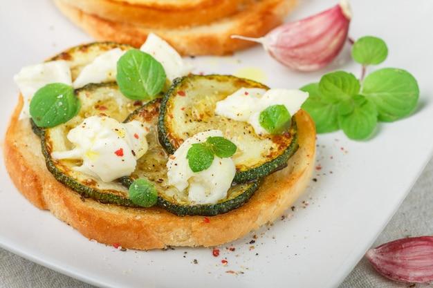 Delikatesse bruschetta mit gebratener oder gebackener zucchini, mozzarella, knoblauch, minze und gewürzen. mediterranes sandwich. Premium Fotos