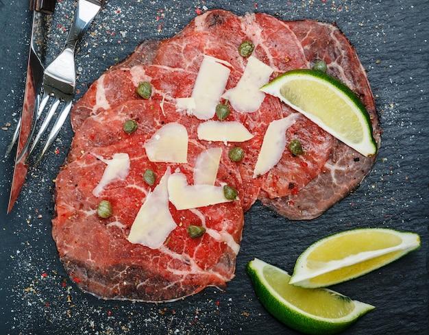 Delikatessen-aperitif aus frischfleisch - carpaccio vom rind mit zitrone oder limette, kapern, parmesan, grobem meersalz und frisch gemahlenem pfeffer auf einer schwarzen schieferplatte Premium Fotos