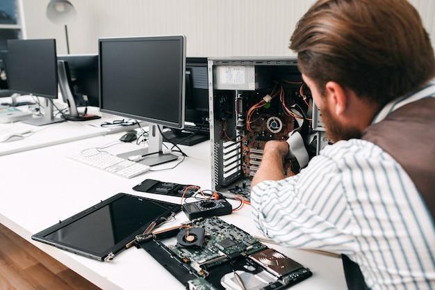 Demontage des computers, nahaufnahme. der mechaniker zerlegt die cpu, um den fehlergrund zu finden. elektronische reparatur, renovierungskonzept Premium Fotos