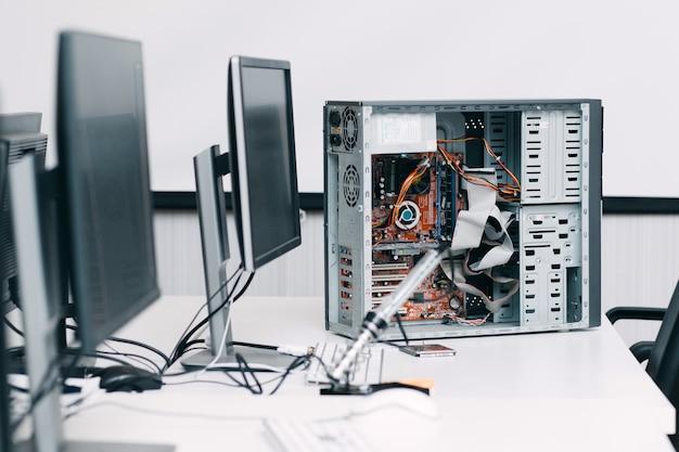 Demontierte computereinheit auf tisch mit monitoren. elektronische reparaturwerkstatt, werkstatt, industrie, renovierungskonzept Premium Fotos