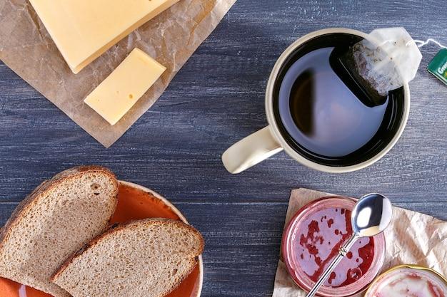 Den tisch zum frühstück vorbereiten. tasse tee und brot mit käse, glas marmelade. Premium Fotos