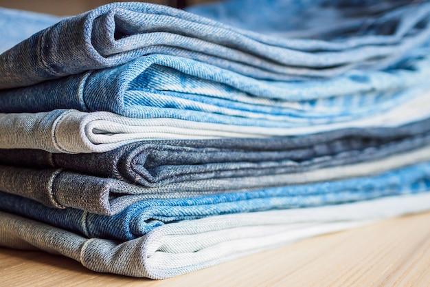 Denim blue jeans stapel auf holztisch hintergrund Premium Fotos