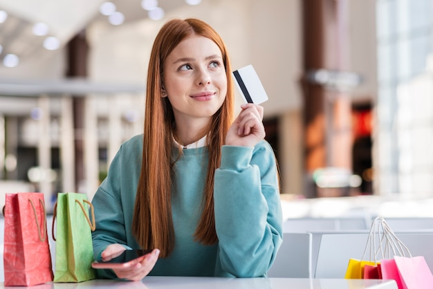Denkende frau, die eine kreditkarte hält Kostenlose Fotos