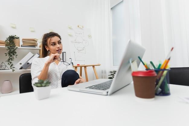 Denkende frau, die in ihrem büro sitzt Kostenlose Fotos