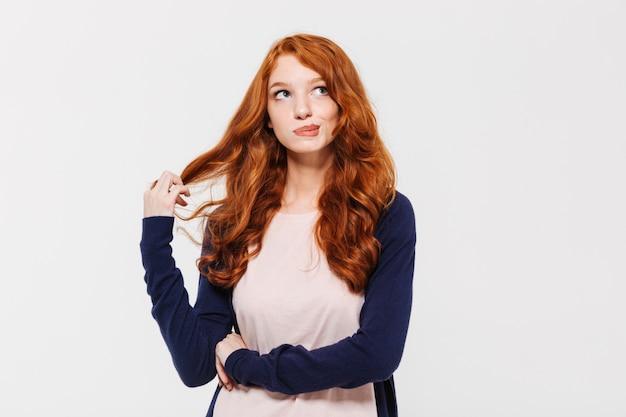 Denkende süße junge rothaarige dame Kostenlose Fotos
