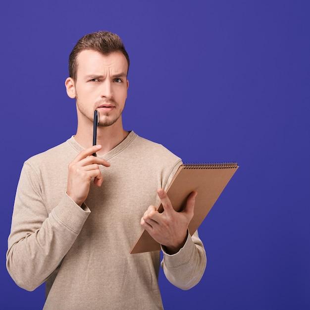 Denkender angestellter mit notizbuch in der linken hand, hält stift nahe gesicht in der rechten hand Premium Fotos