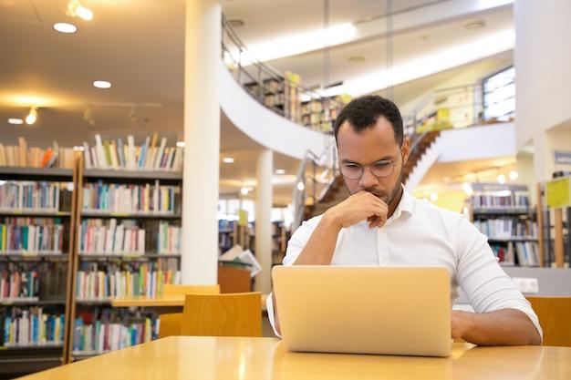 Denkender junger mann, der hand auf kinn hält und laptop betrachtet Kostenlose Fotos