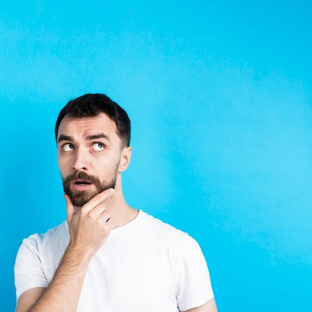 Denkender mann, der mit der hand auf kinn aufwirft Kostenlose Fotos