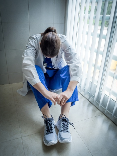 Deprimierte ärztin, die verzweifelt an einem krankenhauskorridor sitzt - gesundheits- und trauerkonzept Kostenlose Fotos