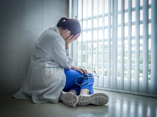 Deprimierte ärztin, die verzweifelt in der nähe eines krankenhausfensters sitzt - gesundheits- und trauerkonzept Kostenlose Fotos