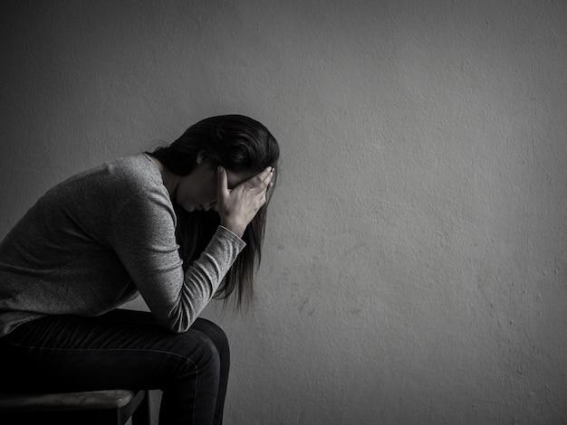 Deprimierte frau, die zu hause auf einem stuhl in der dunkelkammer sitzt. Premium Fotos