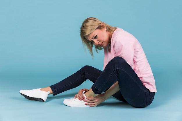 Deprimierte frau mit dem verletzten fuß, der auf blauem hintergrund sitzt Kostenlose Fotos