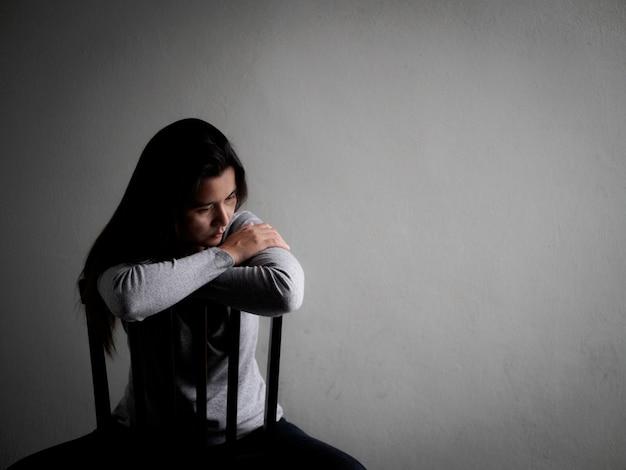 Deprimierte gebrochene herzige frau, die zu hause alleine in der dunkelkammer sitzt. einsam, traurig, liebe Premium Fotos