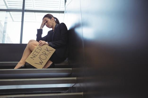Deprimierte geschäftsfrau, die auf treppen sitzt, die kartonblatt mit text halten, brauchen arbeit Premium Fotos