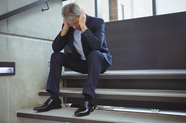 Deprimierter geschäftsmann, der auf treppen sitzt Premium Fotos