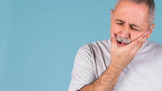 Deprimierter kranker mann, der zahnschmerzen hat und seine backe auf blauem hintergrund berührt Kostenlose Fotos
