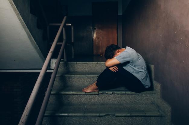 Deprimierter mann. trauriger mann, der ihre knie auf der treppe im gebäude umarmend sitzt Premium Fotos