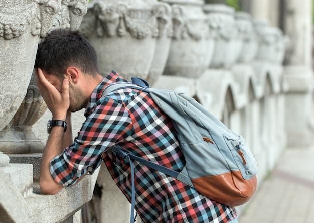 Deprimierter und verzweifelter mann, der sich an die wand lehnt Premium Fotos