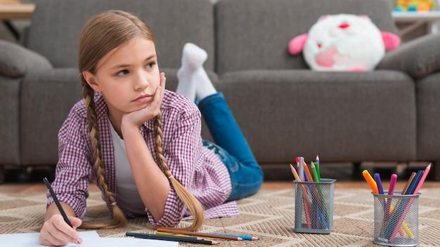 Deprimiertes mädchen, das auf teppichzeichnung mit farbigem bleistift liegt Kostenlose Fotos