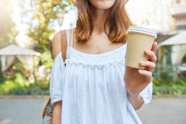 Der abgeschnittene schuss der schönen jungen frau trägt ein weißes sommerkleid, das eine tasse kaffee zum mitnehmen hält und im freien in der altstadt geht Kostenlose Fotos