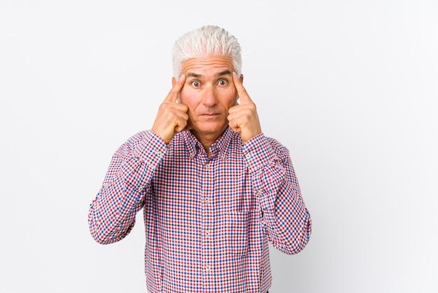 Der ältere kaukasische lokalisierte mann konzentrierte sich auf eine aufgabe und hielt die zeigefinger, die kopf zeigen. Premium Fotos