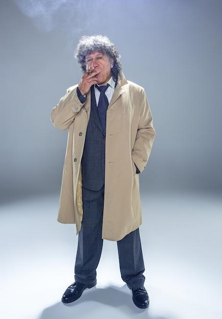 Der ältere mann im umhang mit zigarre als detektiv oder mafia-chef. studioaufnahme auf grau im retro-stil Kostenlose Fotos