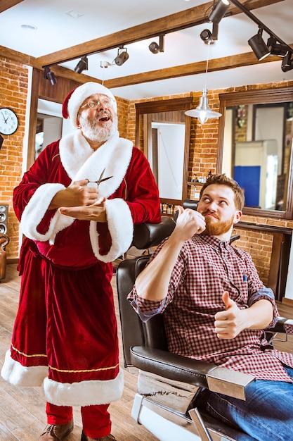 Der ältere mann im weihnachtsmannkostüm, der als persönlicher meister mit schere im friseurladen vor weihnachten arbeitet Kostenlose Fotos