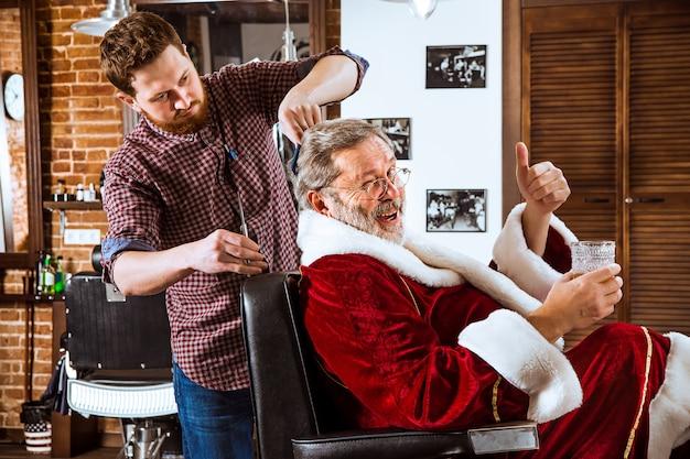 Der ältere mann im weihnachtsmannkostüm rasiert seinen persönlichen meister vor weihnachten im friseurladen Kostenlose Fotos