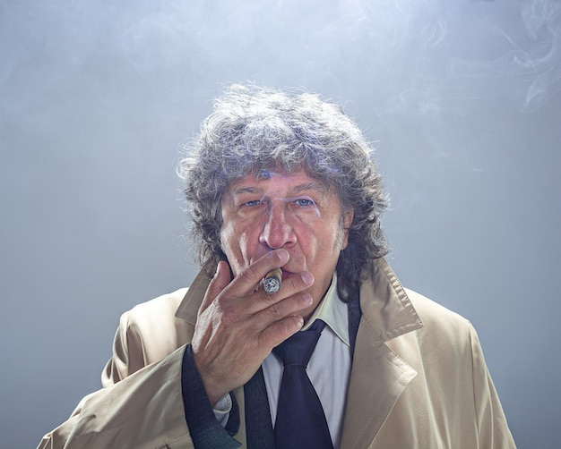 Der ältere mann mit zigarre als detektiv oder chef der mafia auf grauem atelier Kostenlose Fotos