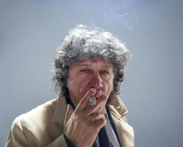 Der ältere mann mit zigarre als detektiv oder chef der mafia im grauen studio Kostenlose Fotos