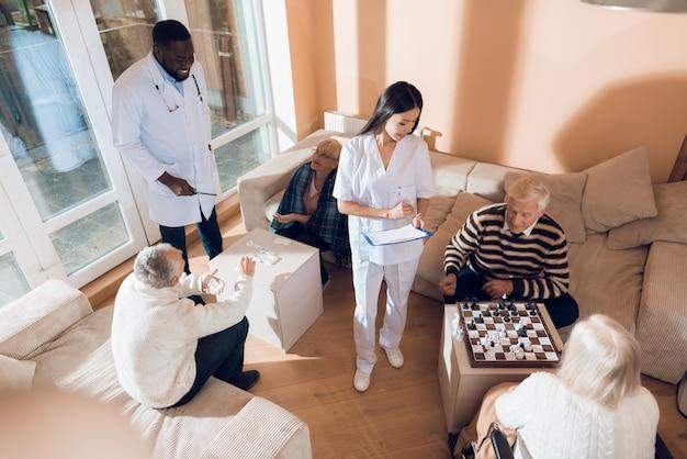 Der ältere mann und die ältere frau spielen schach im pflegeheim. Premium Fotos