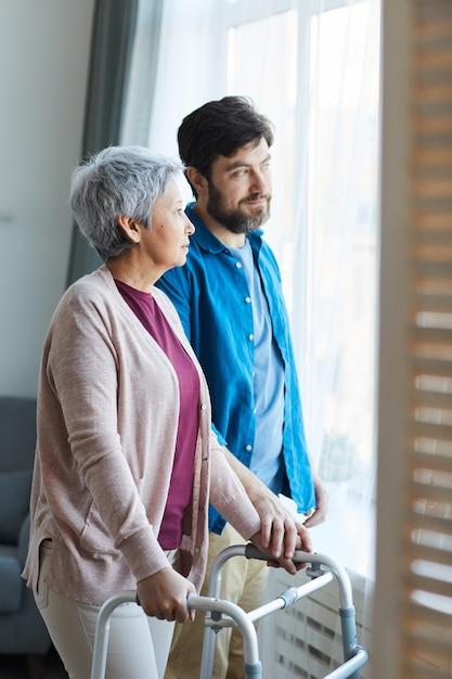 Der ältere sohn kümmert sich um seine ältere mutter, sie stehen am fenster und unterhalten sich zu hause Premium Fotos
