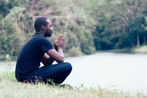 Der afrikanische mann, der für betet, dankt gott mit grüner natur im hintergrund. Premium Fotos