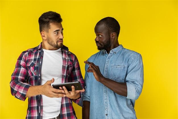 Der afroamerikaner beweist dem europäer etwas in informellen hemden Kostenlose Fotos