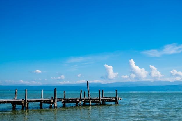 Der alte hölzerne pier am meer mit blauem himmel Premium Fotos
